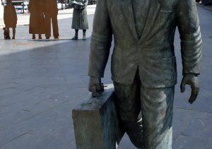 Estatua dedicada al migrante con su familia de fondo en el Puerto de Vigo (Estación Marítima Internacional) (Galicia)